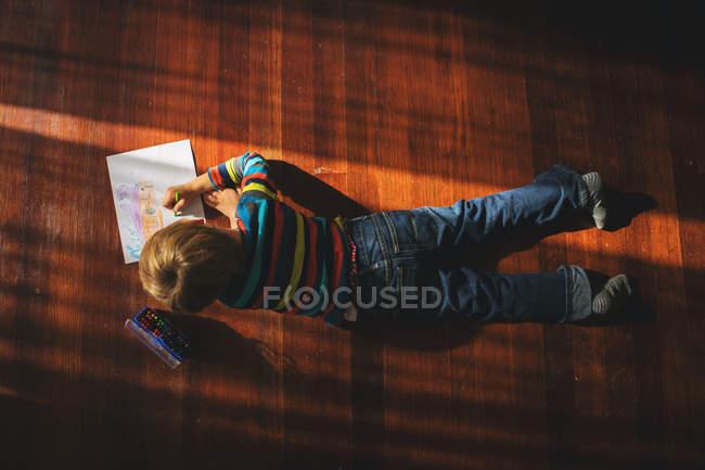Хлопчик лежав на підлозі, нанесення зображення — стокове фото