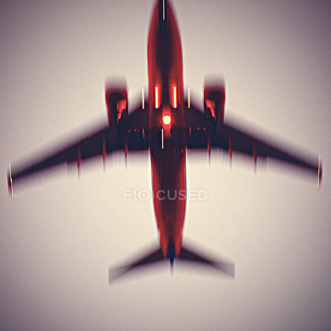 Airplane flying in sunset sky — Stock Photo