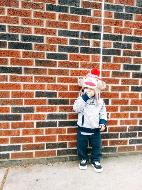 Junge lehnt an Ziegelmauer — Stockfoto