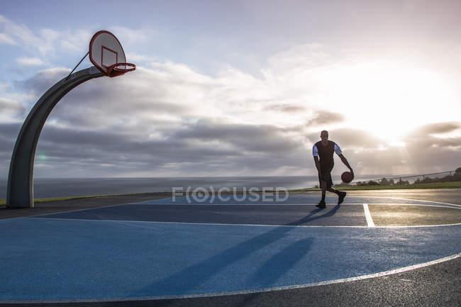 Homme jouant au basket dans le parc — Photo de stock