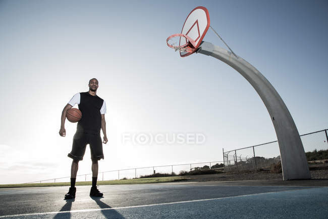 Man holding basketball ball in park — Stock Photo