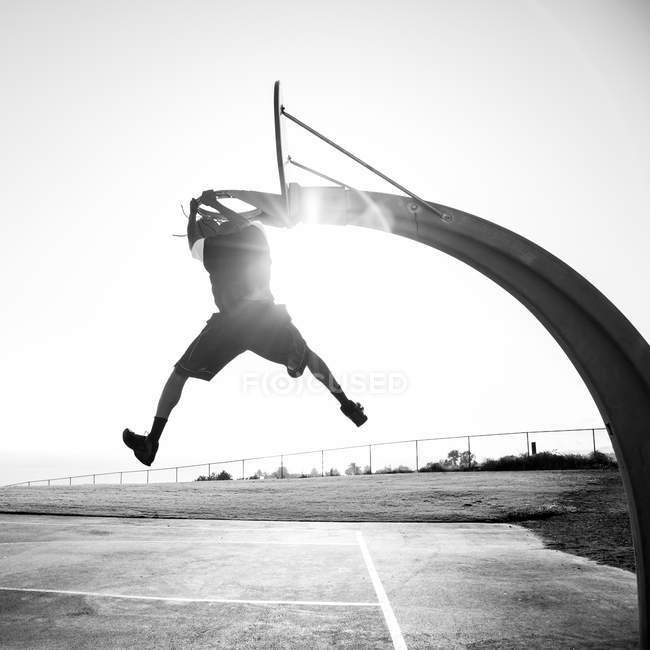 Young man shooting hoops in park — Stock Photo
