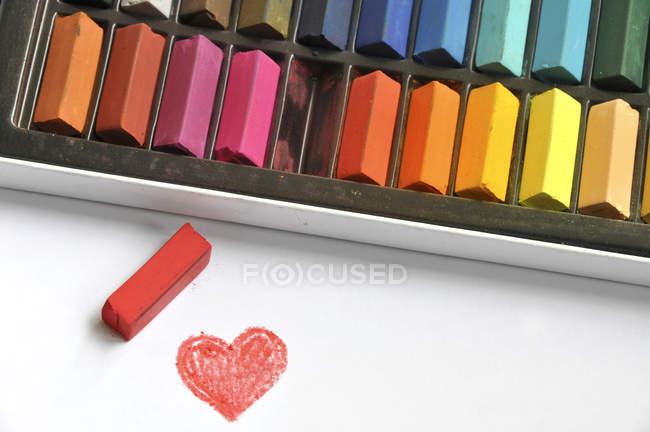 Multi couleur craies et coeur rouge — Photo de stock