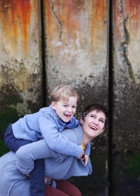 Мати даючи piggyback син — стокове фото