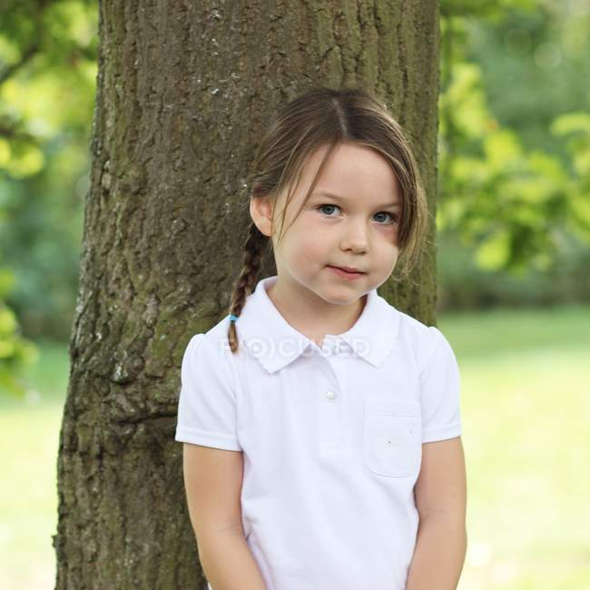 Girl standing by tree — Stock Photo