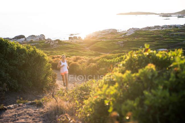 Sendero de mujer corriendo por la costa - foto de stock