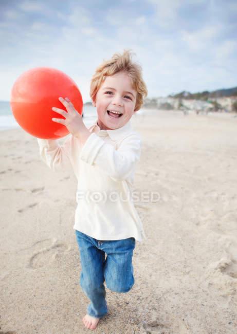 Niño con pelota en la playa - foto de stock