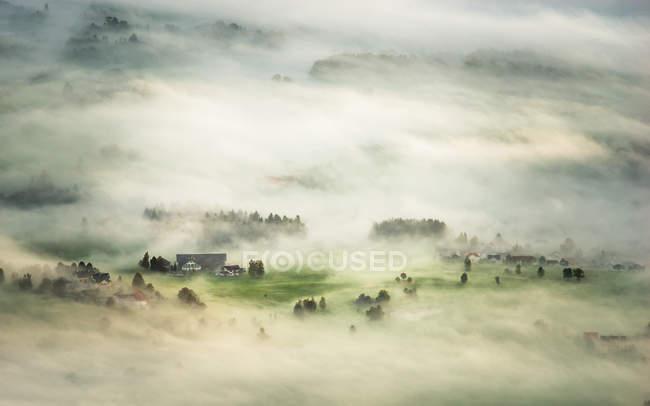 Утренний туман скрывается небольшая деревня — стоковое фото