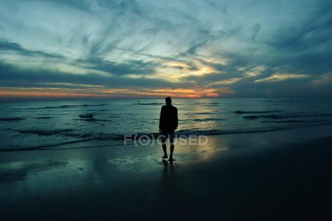 Hombre caminando hacia el mar - foto de stock