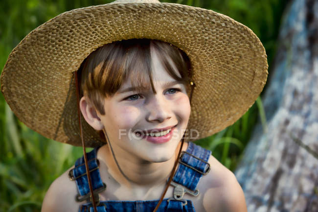 Хлопчик солом'яному капелюсі і посміхається — стокове фото