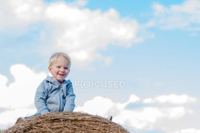 Boy sitting on hay bale — Stock Photo