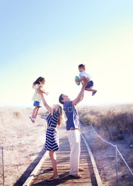 Parents holding kids in air — Stock Photo