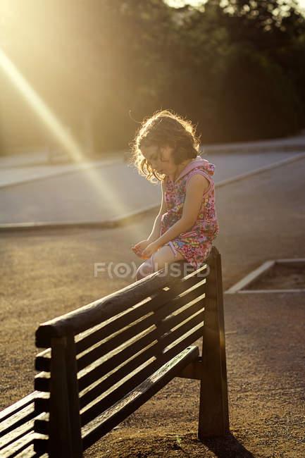Дівчинка сидить на лавці — стокове фото