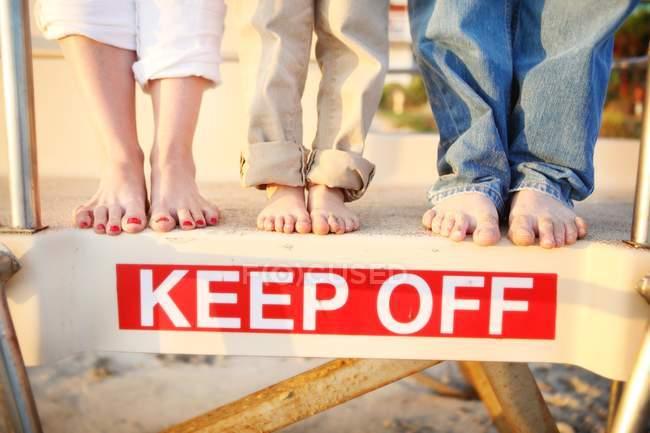 Ноги, стоя на спасателем хижину выше знак — стоковое фото