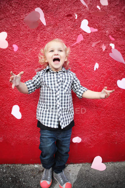 Boy throwing paper hearts in air — Stock Photo