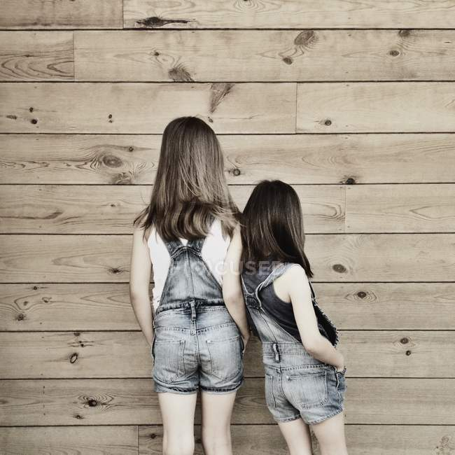 Girls wearing dungarees standing side by side — Stock Photo