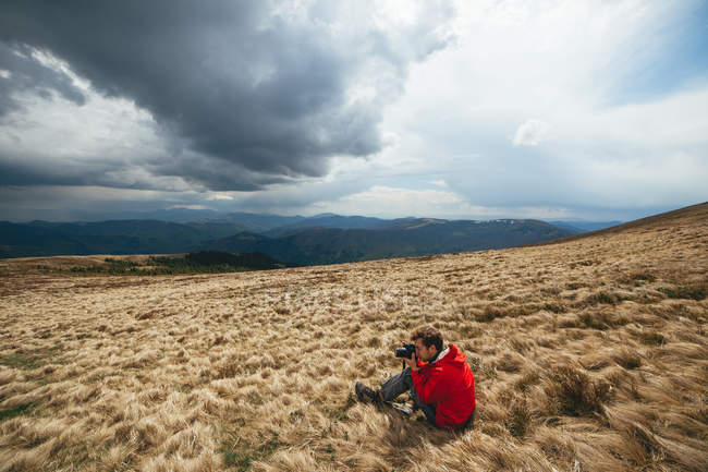 Man sitting on withered grass and photographing — Stock Photo