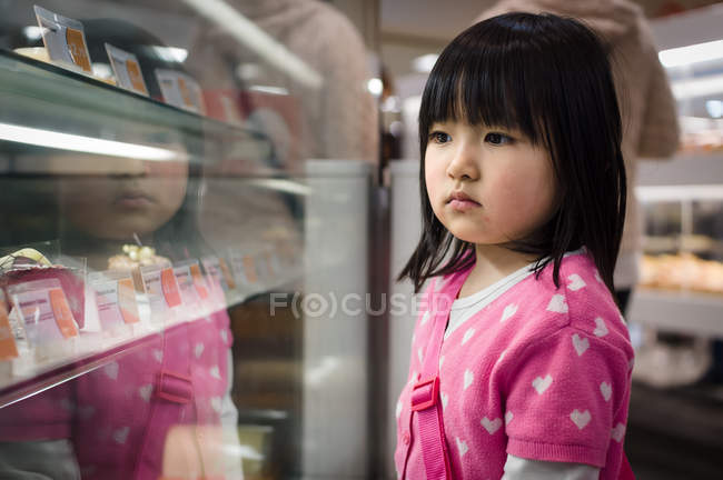 Girl looking at display in shop — Stock Photo