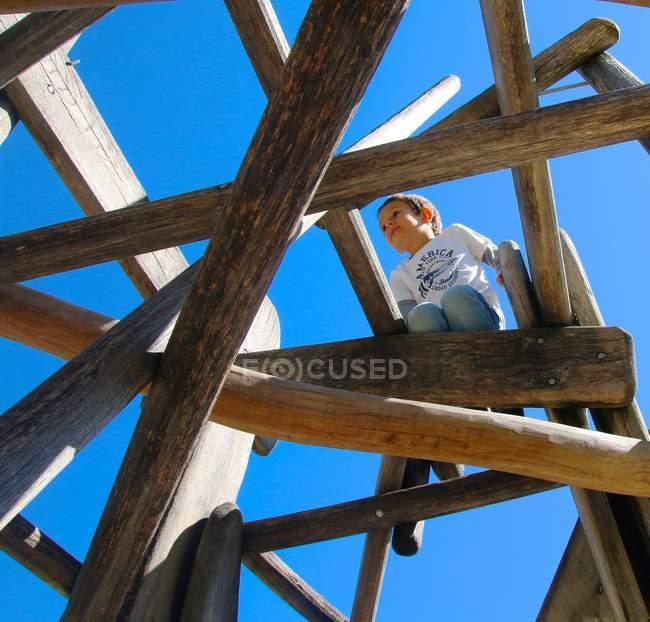 Ragazzo che gioca sul parco giochi in legno — Foto stock
