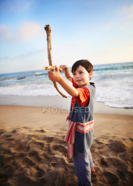 Boy playing with makeshift bow and arrow — Stock Photo