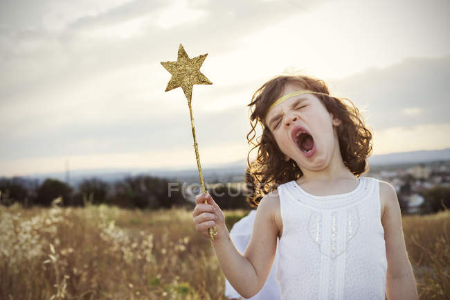 Fille tenant baguette magique et rugissement — Photo de stock