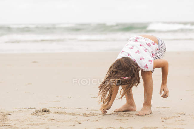 Little girl drawing on sand — Stock Photo