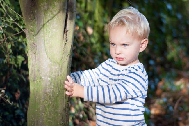Ragazzo in piedi vicino all'albero — Foto stock