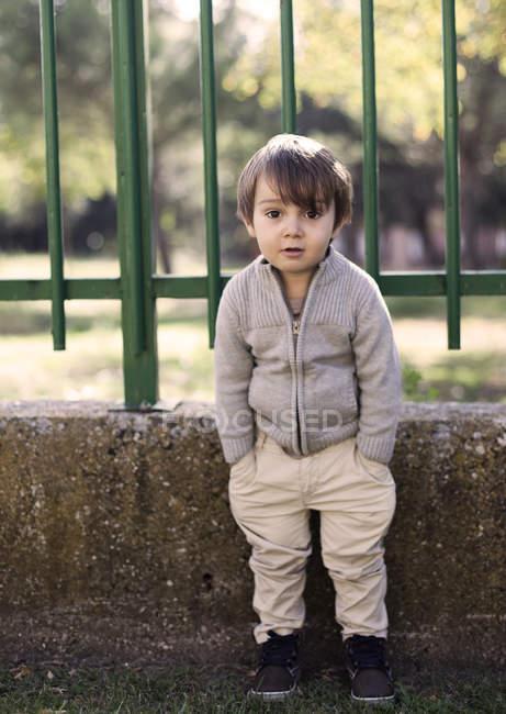 Хлопчик стоїть за межами школи паркан — стокове фото