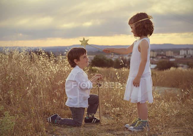 Boy kneeling down in front of girl — Stock Photo