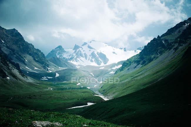 Долина у подножия заснеженных гор — стоковое фото