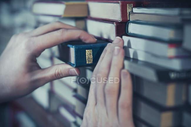 Mains féminines prenant livre de l'étagère — Photo de stock