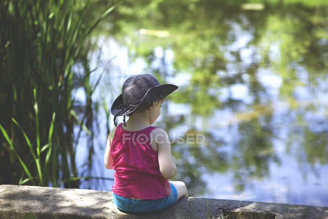 Девушка, сидящая у пруда — стоковое фото