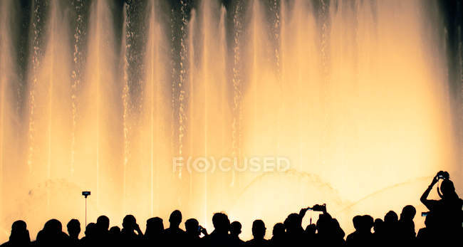 Silhouettes of people in front of illuminated fountain — Stock Photo
