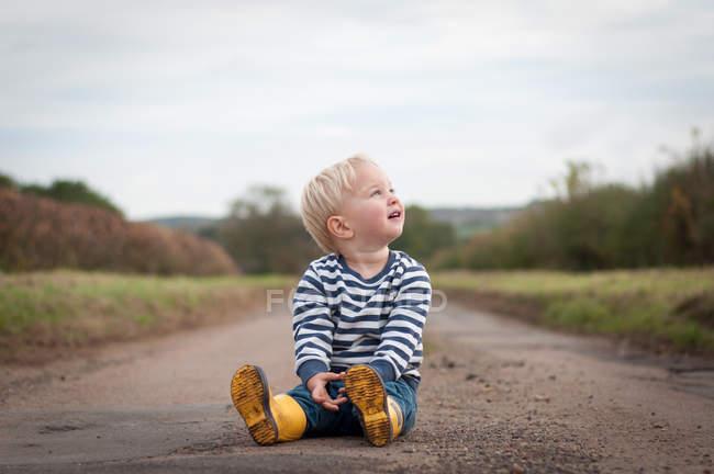 Carefree boy sitting on path — Stock Photo