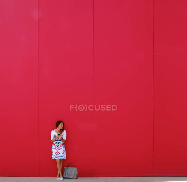 Woman standing in front of red wall — Stock Photo