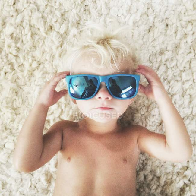 Toddler lying on floor wearing sunglasses — Stock Photo