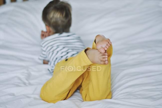 Boy lying on bed — Stock Photo