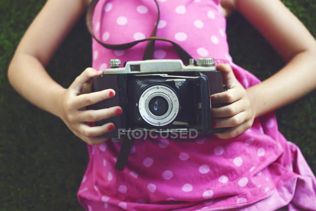 Девушка держит винтажную камеру — стоковое фото