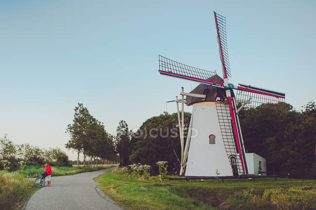 Man standing on road next to windmill — Stock Photo