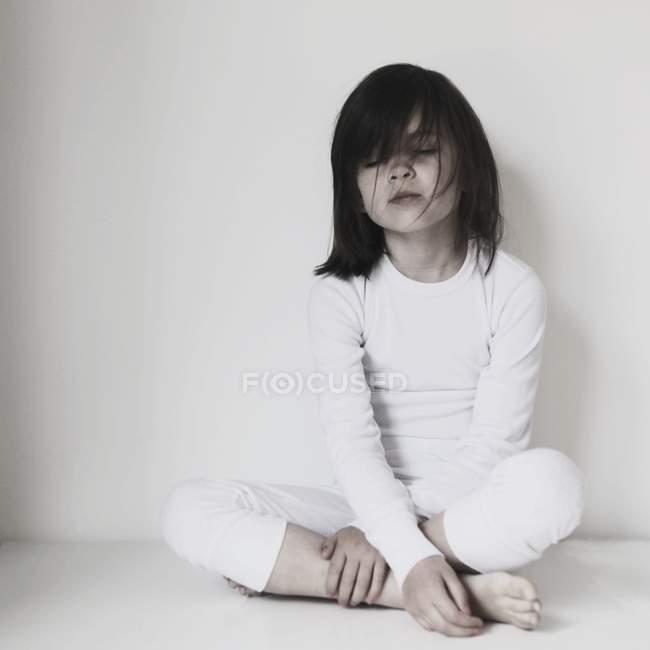 Girl sitting cross-legged with eyes closed — Stock Photo