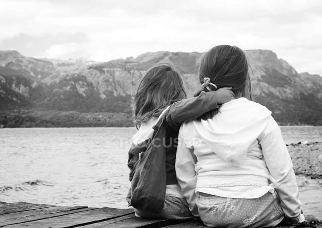 Hermanas sentadas en embarcadero junto al lago - foto de stock