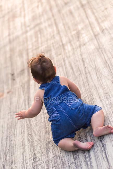 Bambino che striscia su una superficie di legno — Foto stock