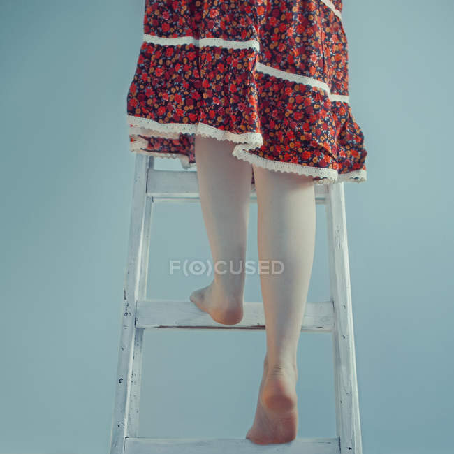 Woman climbing on ladder — Stock Photo