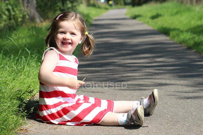 Mädchen sitzt auf Fußweg und lächelt — Stockfoto