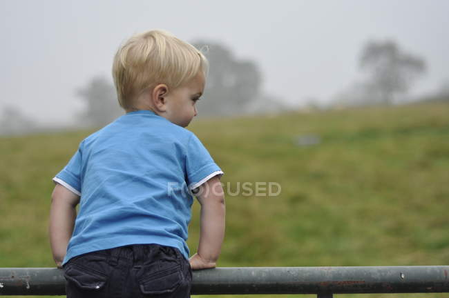 Boy leaning over fence — Stock Photo