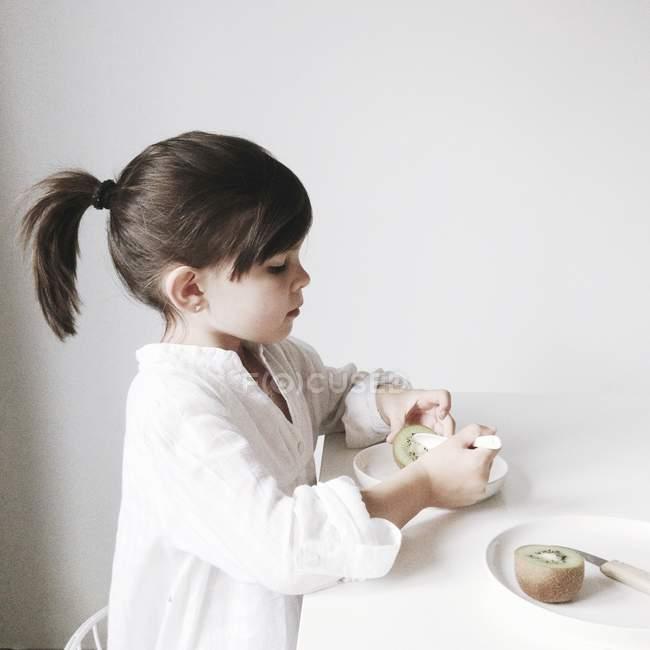 Девушка ест киви в таблице — стоковое фото