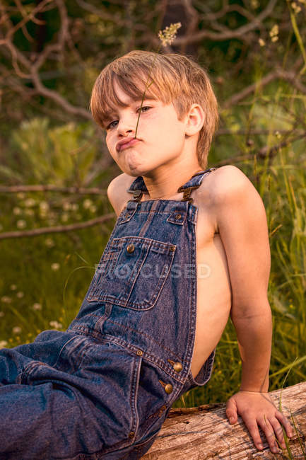 Boy wearing overalls on fallen tree — Stock Photo