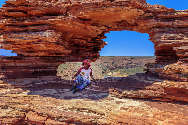 Girl sitting in shadow of arched rock — Stock Photo