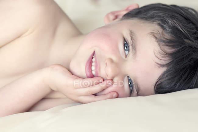 Junge legt sich hin und schaut in Kamera — Stockfoto