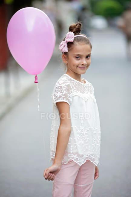 Menina feliz segurando balão rosa — Fotografia de Stock
